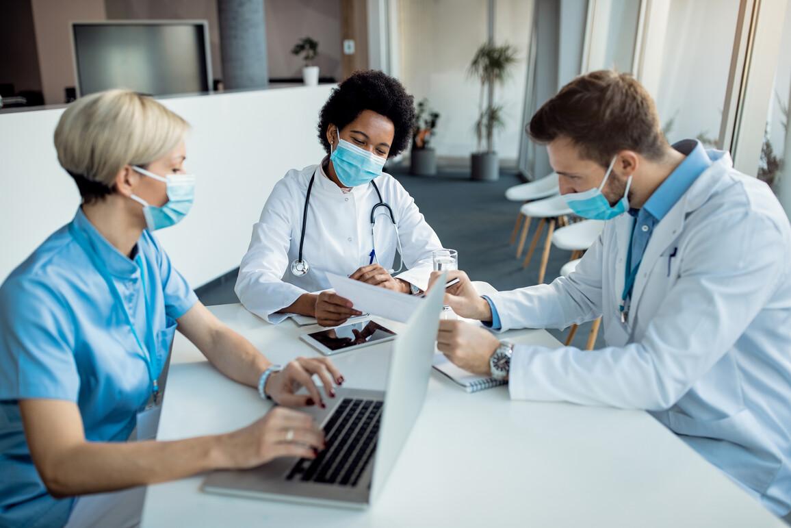 Ärztin analysiert mit ihren Kollegen in der Klinik medizinische Berichte.