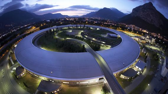 Wie ein Ufo in den Alpen wirkt die ringförmige Halle der ESRF in Grenoble. Hier finden jedes Jahr 6000 Gastforschende exzellente Experimentiermöglichkeiten mit hartem Röntgenlicht vor.