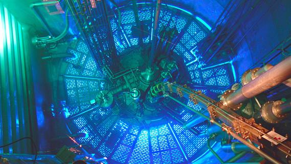 Blick in das Innere des Hochflussreaktors HFR am Institut Laue-Langevin. Unter mehreren Metern Wasser befindet sich der Stahlbehälter, in dem die Neutronen erzeugt werden. Von dort führen Leitrohre seitlich in die Experimentierhalle, in der die Neutronen als Sonden für vielfältige Forschungsfragen dienen.