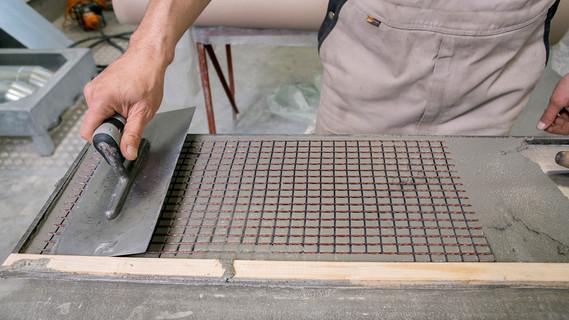 Betonage. Das Carbongelege wird in mehreren Lagen in Feinbeton eingearbeitet.