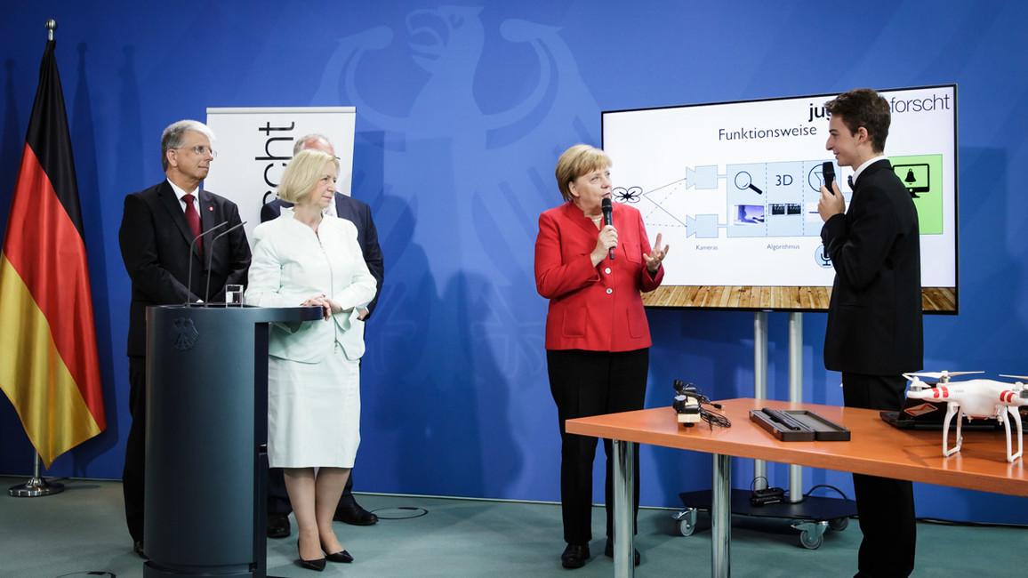 Preisträger Tassilo Schwarz stellt Bundeskanzlerin Merkel und Bundesforschungsministerin Wanka sein Forschungsprojekt vor.