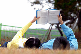 Zwei junge Menschen liegen im Gras und lesen ein Buch