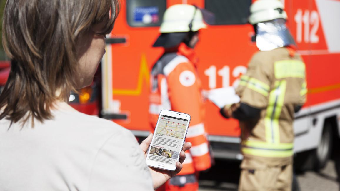 Eine junge Frau hält ein Handy in ihrer Hand; im Hintergrund sieht man Mitglieder der Feuerwehr.