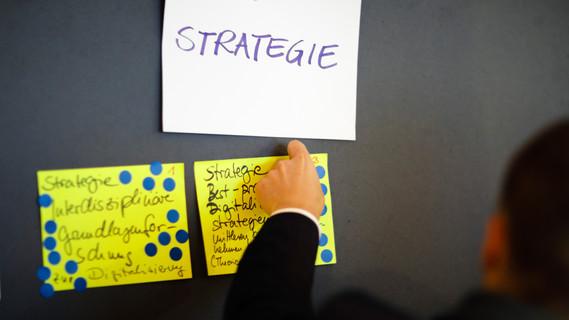 Eine Hand befestigt eine Moderationskarte an einer Pinnwand.