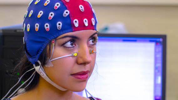 Auf dem Bild ist eine Frau mit einer speziellen Sensorenkappe zu sehen, die die Spannungsschwankungen auf der Kopfhaut misst.