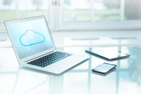 Laptop, Tablet und Smartphone auf einem Tisch vor einem Fenster