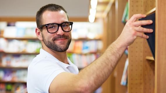 Junger Mann zieht ein Buch aus einem Regal in einer Bibliothek