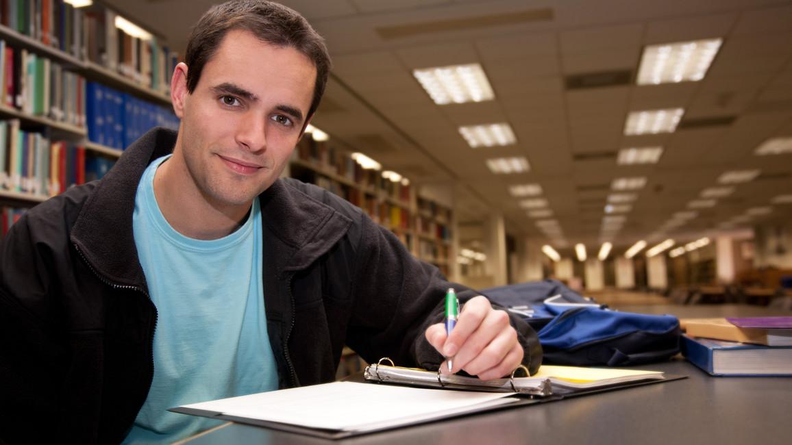 Junger Mann in einer Bibliothek