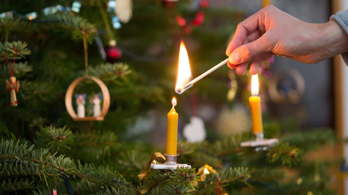 Frau zündet Kerze an Weihnachtsbaum an
