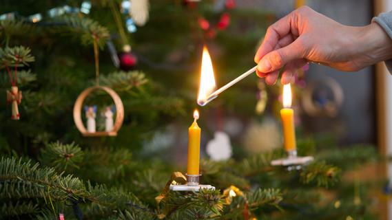 Eine Frau zündet mit einem Streichholz am 25.12.2014 in Muenchen eine Kerze an einem Christbaum an.