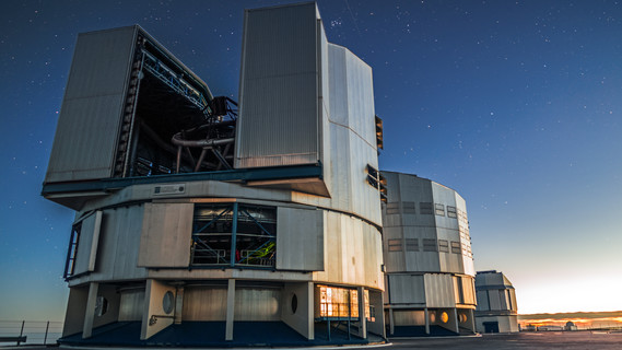 Fenster zum Universum: das Very Large Telescope auf dem 2600 Meter hohen Cerro Paranal in der chilenischen Atacama-Wüste. Der Sonnenuntergang wirft seine Strahlen auf das Very Large Telescope. Eines der Hauptteleskope hat seine Tore geöffnet. Erste Sterne erscheinen am klaren Abendhimmel.