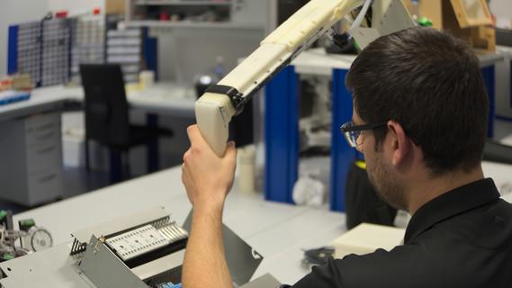 Das Bild zeigt, wie ein Mitarbeiter der TH Nürnberg mit einem Gelenkroboter zusammenarbeitet.