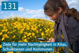 Ein Mädchen steht auf dem Feld und betrachtet Blüten durch eine Lupe.