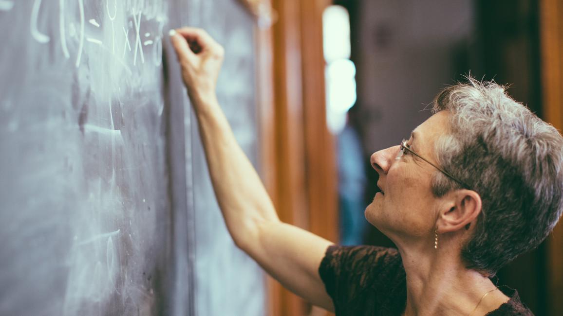 Mathematik-Lehrerin schreibt Formeln mit Kreide an die Tafel
