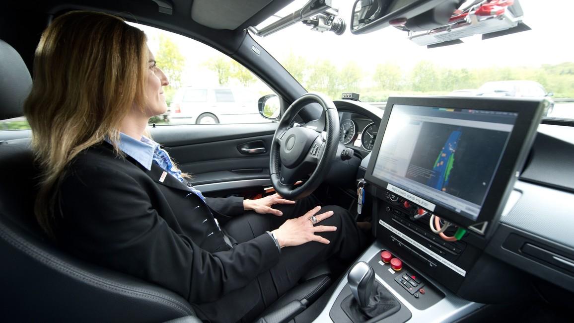 Junge Frau in einem Testfahrzeug für automatisiertes Fahren