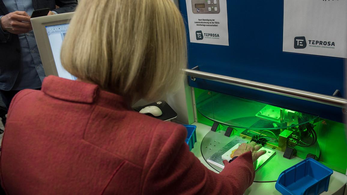 Tag 1: Bundesforschungsministerin Wanka steht bei Teprosa selbst an der Werkbank und fertigt auf Knopfdruck per Laseraktivierung ein Bauteil.