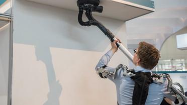 Das am Oberkörper getragene Unterstützungssystem erleichtert das Arbeiten in und über Kopfhöhe.