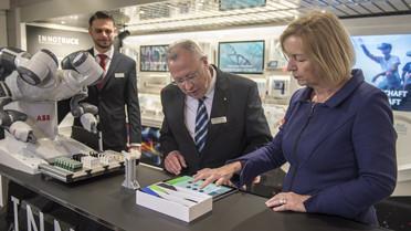 Ein Roboter stellt Computer-Chips für ein Armband her. Bundesforschungsministerin Wanka gibt dem Roboter mittels Touchpad Anweisungen.
