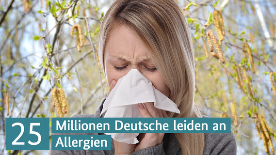 Eine Frau putzt sich die Nase. Im Hintergrund sind blühende Birken zu sehen.