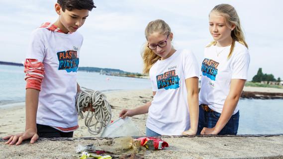 Zwei Mädchen und ein Junge betrachten gefundenen Plastikmüll
