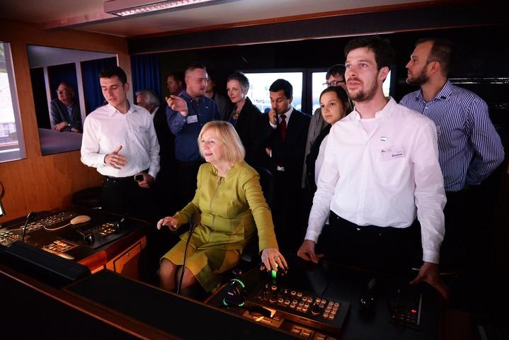 Tag 3: Ministerin Wanka zeigt sich beeindruckt vom Fahrsimulator. Die Reaktionszeit sei ganz schön schwierig, sagt sie.