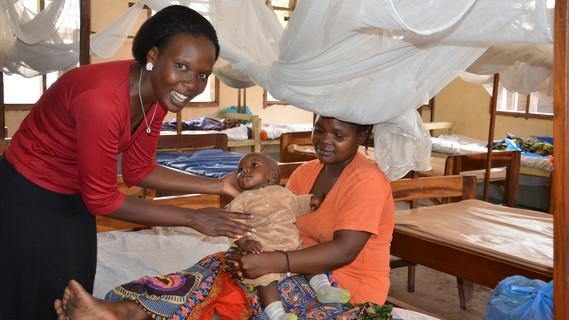 Zwei Frauen umsorgen ein Kleinkind in einer Klinik.