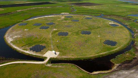 Kreisförmige Insel mit einem Durchmesser von rund 150 Metern in einer flachen Weidenlandschaft, die nur durch einen schmalen Graben von den umgebenden Feldern getrennt ist. Auf der Insel befinden sich mehrere Antennenfelder in zwei verschiedenen Bauarten.