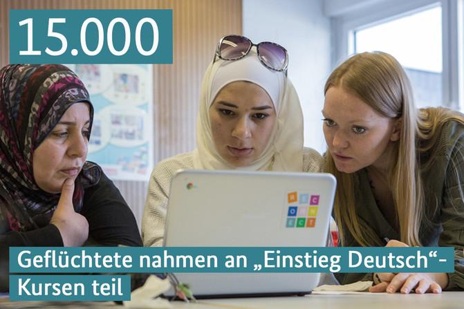 Drei Frauen sitzen vor einem Laptop.
