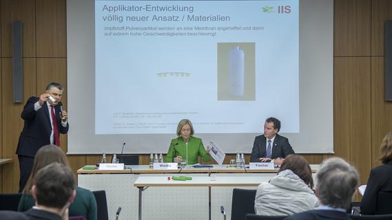 Johanna Wanka, Bundesministerin für Bildung und Forschung, und Stefan Henke, Geschäftsführer der IIS GmbH, stellen gemeinsam in Berlin den Prototyp eines nadelfreien Impfsystems vor