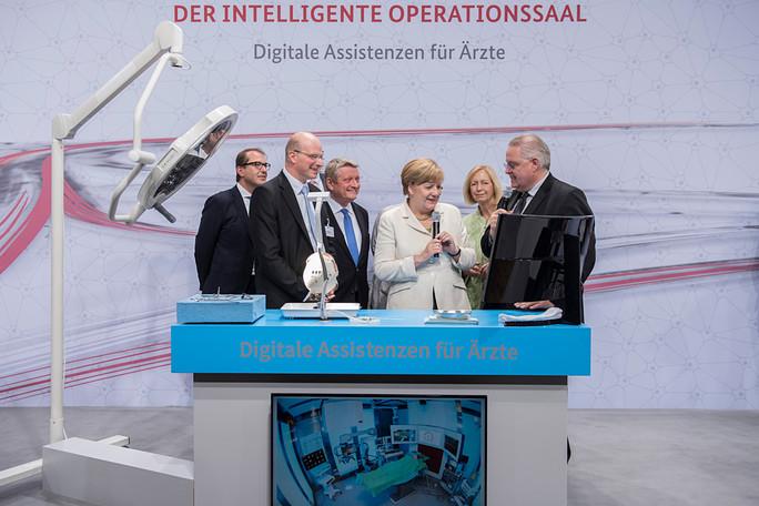 Thomas Neumuth (links) und Andreas Melzer von der Universität Leipzig präsentieren der Bundeskanzlerin den Intelligenten OP