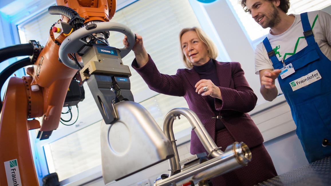 """Bundesforschungsministerin Johanna Wanka im """"Future Work Lab"""", einer Modellfabrik, die das Zusammenspiel von Mensch und moderner Technik erforscht. Um die """"Zukunft der Arbeit"""" dreht sich auch alles im Wissenschaftsjahr 2018."""