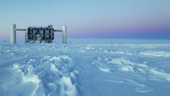 Das Neutrino-Observatorium IceCube bei der Amundsen-Scott-Südpolstation in der Antarktis. Das Bild zeigt das Datenzentruman der Eisoberfläche – das Neutrinoteleskop selbst ist mit seinen 5160 Lichtsensoren bis zu 2,5 Kilometer tief im Eis versenkt.