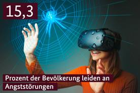 Eine Frau mit einer Virtuel-Reality Brille berührt die Projektion einer Spinne