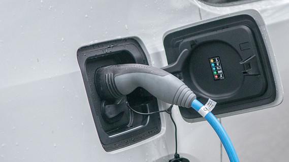Ein Elektrofahrzeug ist in Berlin an eine Ladestation angeschlossen.