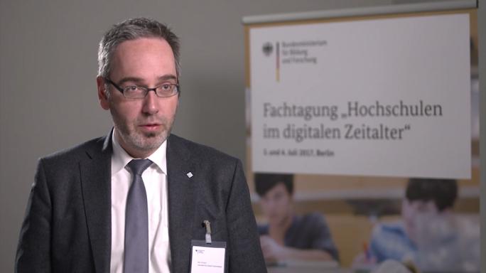 """Poster zum Video """"Digitale Hochschulbildung"""": Experteninterview mit Jan Gerken (Kanzler*innenvereinigung)"""