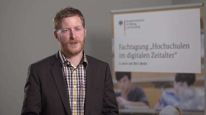 """Poster zum Video """"Digitale Hochschulbildung"""": Experteninterview mit Prof. Dr. Bernhard Schmidt-Hertha (Eberhard Karls Universität Tübingen)"""