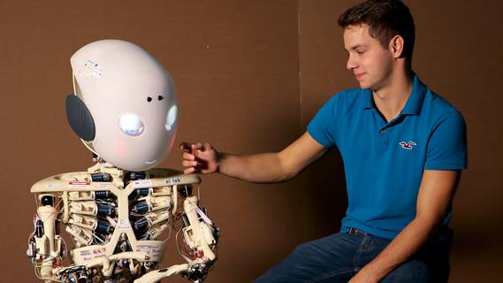 Ein Mitarbeiter im Gespräch mit Roboy, einem humanoiden Roboter