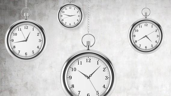 Man sieht Uhren, die verschiedene Uhrzeiten anzeigen.