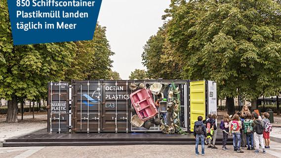 Ein Schiffscontainer mit Plastikmüll steht als Installation in einer Fußgängerzone.