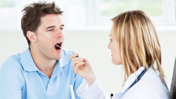 Ärztin entnimmt einem Patienten eine Speichelprobe mit einem Wattestäbchen.