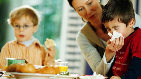 Mutter putzt Kind am Frühstückstisch die Nase.