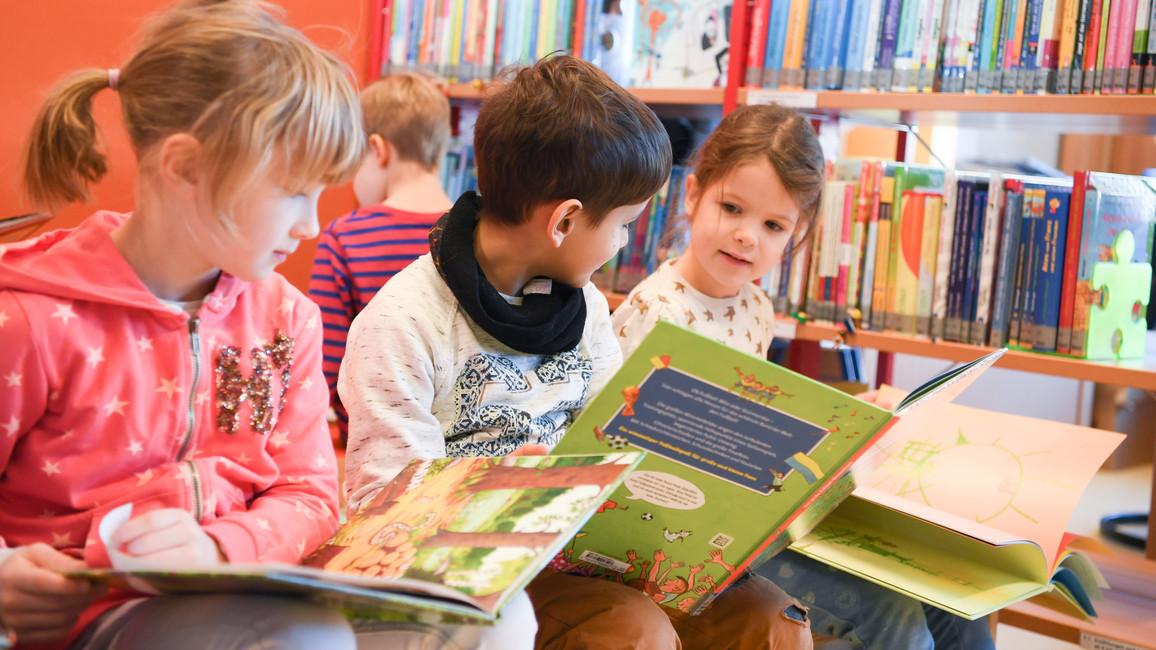 Schüler der Klasse 1/2 a der Marie-Curie-Grundschule lesen in der neuen Schulbibliothek der Schule in Frankfurt am Main (Hessen) Bücher.