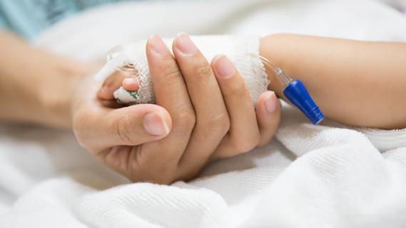 Eine Mutter hält die Hand ihres Kindes